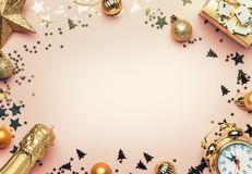 Christmas or New Year composition, frame, pink background with g. Old Christmas decorations, stars, snowflakes, balls, alarm clock, gift box and bottle of royalty free stock photography