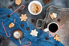 Christmas or New year composition. Gingerbread, candy cane and coffee cup on dark background. Flat lay. Top view Stock Image
