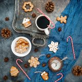 Christmas or New year composition with gingerbread, candy cane and coffee cup on dark background. Food concept. Flat lay. Top view Royalty Free Stock Photo