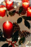 Christmas and New Year composition. Lit candles, fir cones and branch of holly. Bokeh, low-key lighting, selective focus stock image