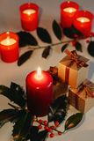 Christmas and New Year composition. Lit candles, gift boxes and branch of holly. Low-key lighting, selective focus royalty free stock image