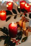 Christmas and New Year composition. Lit candles, present boxes and branch of holly. Bokeh, low-key lighting, selective focus stock images