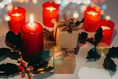 Christmas and New Year composition. Lit candles, present boxes and branch of holly. Bokeh, low-key lighting, selective focus royalty free stock photography