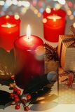 Christmas and New Year composition. Lit candles, present boxes and branch of holly. Bokeh, low-key lighting, selective focus stock photos