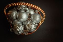 Basket with Christmas decorations on black background Stock Photos