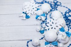 Christmas or new year composition in silver white and blue colors with balls snowflake bows and beads on white wood.  royalty free stock photography