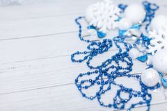 Christmas or new year composition in silver white and blue colors with balls snowflake bows and beads on white wood.  stock images