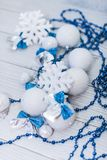 Christmas or new year composition in silver white and blue colors with balls snowflake bows and beads on white wood.  stock photos