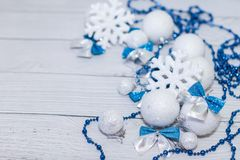 Christmas or new year composition in silver white and blue colors with balls snowflake bows and beads on white wood.  stock photography
