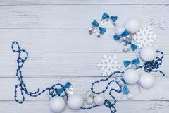 Christmas or new year composition in silver white and blue colors with balls snowflake bows and beads on white wood. Floor stock photography