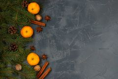 Christmas New Year composition with tangerines, anise, nuts, cinnamon sticks and green fir tree branches on a dark background. Holiday decoration. Top view stock images