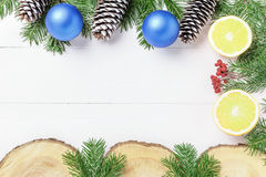 Christmas New Year composition with tangerines, cones, nuts, wicker basket and fir branches in rustic style on old Royalty Free Stock Images