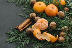 Christmas New Year Composition with Tangerines Pine cones Greens nuts cinnamon on Black Background Holiday Decoration Toned Royalty Free Stock Photo