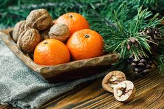 Christmas New Year composition winter holiday celebration concept symbol tangerines mandarin clementine nuts pine cones fir branch. Es rustic style old wooden Royalty Free Stock Image