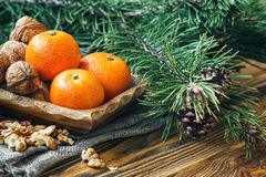 Christmas New Year composition winter holiday celebration concept symbol tangerines mandarin clementine nuts pine cones fir branch. Es rustic style old wooden Royalty Free Stock Photography
