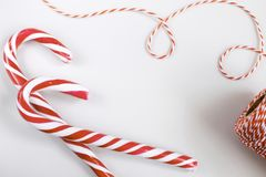 Christmas or New Year concept - Candy canes and twisted cord. Christmas or New Year concept - Candy canes and twisted red and white cord. White background, top royalty free stock photo