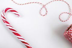 Christmas or New Year concept - Candy canes and twisted cord. Christmas or New Year concept - Candy canes and twisted red and white cord. White background, top stock photography