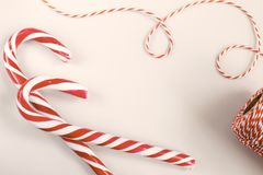 Christmas or New Year concept - Candy canes and twisted cord. Christmas or New Year concept - Candy canes and twisted red and white cord. White background, top stock photo