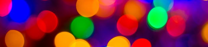 Defocused abstract multicolored bokeh lights wide banner background. Blue, purple, green, orange colors. - christmas and new year royalty free stock images