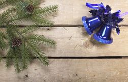 Christmas and New Year Concept. Fir tree branch with cones and toy glass hand bell on wooden board, Top view, flat lay royalty free stock photo