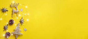 Christmas and new year concept. Greeting banner with copyspace. Shiny silver deer, stars, fir-tree, garland, bokeh on yellow. Background. Top view, flat lay stock image