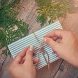 Christmas, new year concept. Hands with Gift for holidays. Gifts, different winter plants on wood background. Flat lay, top view royalty free stock photos