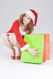 Christmas and New Year Concept and Ideas. Looking Young Caucasian Red Haired Female in Santa Hat Posing With Shopping Bags Royalty Free Stock Images