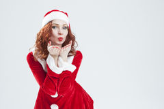 Christmas and New Year Concept and Ideas. Sexy Looking Young Caucasian Red Haired Female Sending Air Kiss Royalty Free Stock Photos