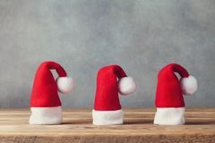 Christmas and New year concept with little Santa Claus hats on wooden background. Holiday greeting card. stock image
