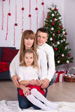 Christmas and New year concept - parents and daughter with decor Stock Photos
