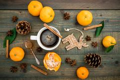 Christmas or New Year concept with pine cones, coffee cup, mandarin and cinnamon on wooden table. Flat lay, top view. Christmas or New Year concept with pine Royalty Free Stock Photos