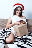 Christmas New Year Concept, sexy model in santa hat with present. S, cute girl with gift write message with phone Stock Photos