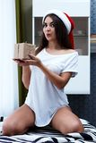 Christmas New Year Concept, sexy model in santa hat with present. S, cute girl with gift Stock Photography