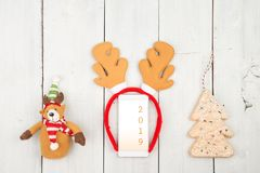 Christmas and new year concept - smartphone with deer horns and text. `2019` on white wooden desk stock photo