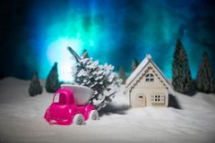 Christmas or New Year concept. Toy car carrying a Christmas tree through the forest in snowfall. Holiday decorated background. Selective focus stock photography