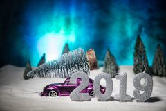 Christmas or New Year concept. Toy car carrying a Christmas tree through the forest in snowfall. Holiday decorated background. Selective focus royalty free stock image