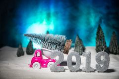 Christmas or New Year concept. Toy car carrying a Christmas tree through the forest in snowfall. Holiday decorated background. Selective focus royalty free stock photos