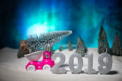 Christmas or New Year concept. Toy car carrying a Christmas tree through the forest in snowfall. Holiday decorated background. Selective focus royalty free stock photography