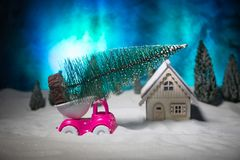 Christmas or New Year concept. Toy car carrying a Christmas tree through the forest in snowfall. Holiday decorated background. Selective focus stock photos