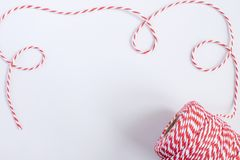 Christmas or New Year concept - twisted red and white cord. Isolated, white background, top view, copy space stock image