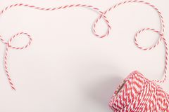 Christmas or New Year concept - twisted red and white cord. Isolated, white background, top view, copy space stock photography