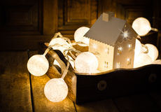 Christmas and New Year cotton ball light garland in a vintage wood tray and a candle holder in shape of a house, sparkling stock image