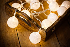 Christmas and New Year cotton ball light garland in a vintage wood tray, on planked wood background, rustic minimalist style royalty free stock photos