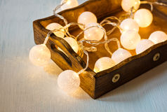 Christmas and New Year cotton ball light garland in a vintage wood tray, shining, close up, bright lights stock photos