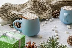 Christmas and New Year cozy holiday composition with gift boxes, cinnamon, scarf, pine cone, mugs with cocoa or stock photo