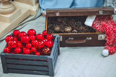 Christmas and New Year decorated close up. Wooden box with pine. Cones .Vintage Christmas Red Ornaments in their original box Royalty Free Stock Photography