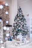 Christmas and New Year decorated interior room with presents and New year tree and toy wooden deer close up. Copy space.  Stock Images