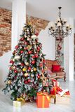 Christmas and New Year decorated interior room with red presents and New year tree and classic brown sofa in front of. White wall Royalty Free Stock Image