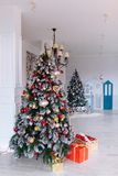 Christmas and New Year decorated interior room with red presents and New year tree in front of white wall. Christmas and New Year decorated interior room with Stock Photo