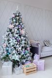Christmas and New Year decorated purple interior room with presents and New year tree and sofa royalty free stock images
